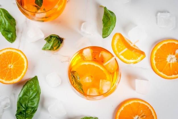 夏の爽やかなドリンク、レモネード、オレンジとバジルのカクテル。白い大理石のテーブルで、コピースペース平面図