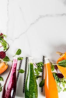 ビーガンダイエット食品。カラフルな新鮮な有機スムージーの選択は、秋野菜と一緒に飲みます:ビートルート、カボチャ、ニンジン、葉物野菜。ボトル、白いテーブル。コピースペースのトップビュー
