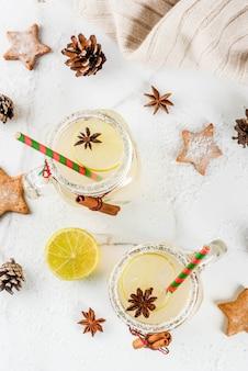 秋と冬の飲み物。クリスマスの休日の飲み物。ライムジュース、シナモン、リキュール、砂糖、アニスの星が付いたお祝いスノーボールカクテル。クリスマスの装飾が施された白いテーブルに、コピースペース平面図