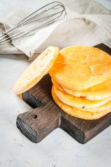 健康的な食事。低グルテングルテンフリーの非アレルギースナックの概念。自家製の焼きたてのトルティーヤは、卵とクリームチーズからパンを曇らせます。明るいコンクリートテーブルコピースペース