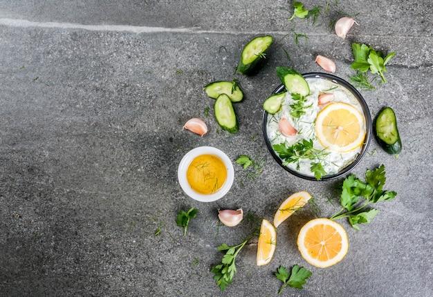 Традиционная кавказская и греческая еда. соус цацики с ингредиентами - огурец, лимон, петрушка, укроп, чеснок. на темном каменном столе. вид сверху копией пространства