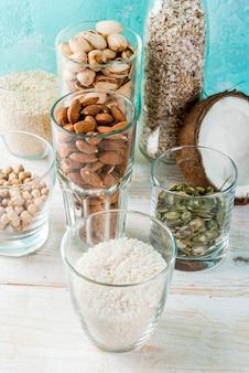 ビーガン代替食品、非乳牛乳のさまざまな成分のセット-米、ココナッツ、アーモンド、ピスタチオ、ゴマ、カボチャの種、大豆、ナッツ、オートミール、明るい青の背景、コピースペース
