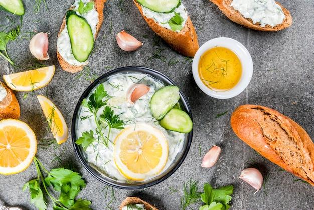 Традиционная кавказская и греческая еда. соус цацики с ингредиентами - огурец, лимон, петрушка, укроп, чеснок. на темном каменном столе. с бутербродами и багетом. вид сверху