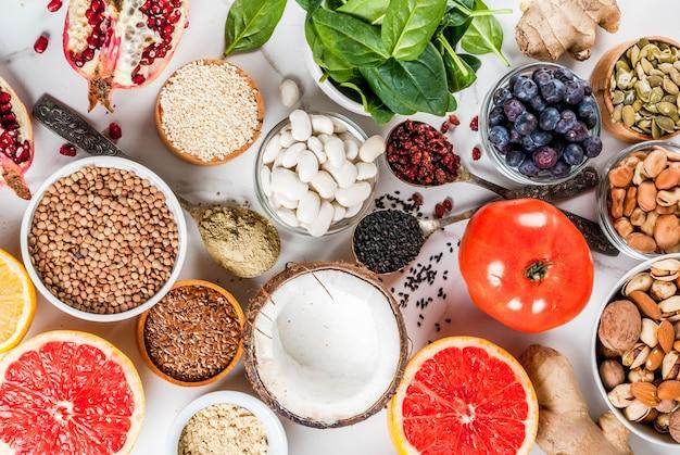 Набор органических здоровой диетической пищи, суперпродуктов - бобы, бобовые, орехи, семена, зелень, фрукты и овощи ... белый фон копией пространства