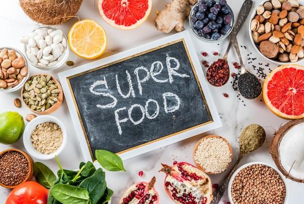 有機健康ダイエット食品、スーパーフード-豆、マメ科植物、ナッツ、種子、野菜、果物、野菜のセット。ホワイトバックグラウンドコピースペース。トップビューフレーム