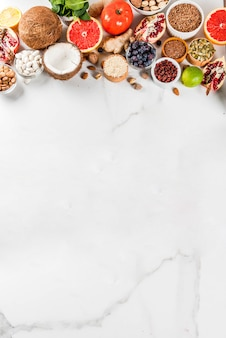 有機健康ダイエット食品、スーパーフード-豆、マメ科植物、ナッツ、種子、野菜、果物、野菜のセット。ホワイトバックグラウンドコピースペース。上面図