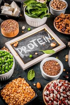 Здоровая диета, веганская пища, источники растительного белка: тофу, веганское молоко, бобы, чечевица, орехи, соевое молоко, шпинат и семена. вид сверху на белом столе.