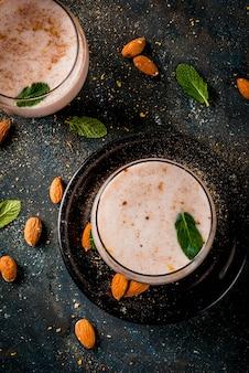 インドの伝統的な飲み物、ホーリー祭の食べ物、ナッツ、スパイス、ミント入りタンダイサルダイミルクドリンク。暗い青色の背景、コピースペース