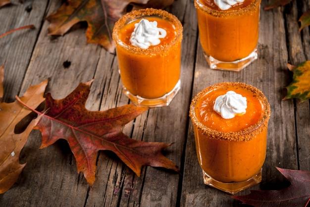 秋の飲み物。感謝祭、ハロウィーンのアイデアとレシピ。アルコールカクテルパンプキンパイウォッカショット秋の古い素朴な木製のテーブルの上の葉、コピースペース