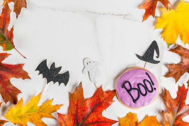 ハロウィーン、碑文ブーとジンジャーブレッドクッキーと白い大理石のテーブルのお祭りの背景!、休日のシンボル(バット、魔女帽子、幽霊)と秋の赤黄色の葉、トップビューコピースペースフレーム