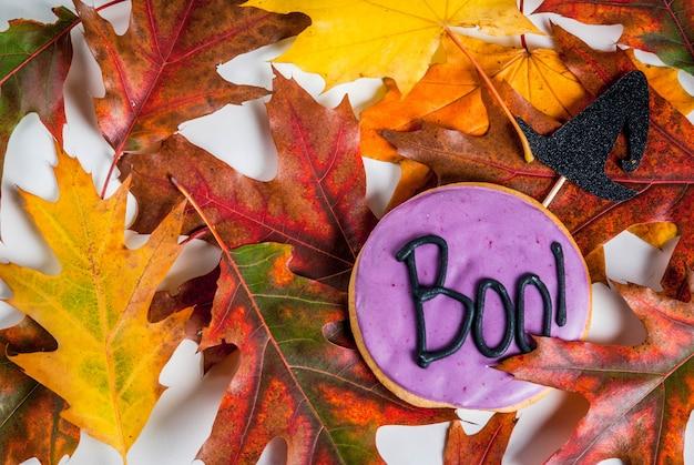 ハロウィーンのお祭りの背景、碑文ブーとジンジャーブレッドクッキーと白い大理石のテーブル!、休日のシンボル(魔女帽子)、トップビューコピースペース