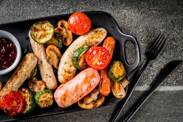 バーベキュー。野菜バーベキュー-キノコ、トマト、ズッキーニ、玉ねぎと様々な肉のグリルソーセージの品揃え。黒い石のテーブルの上、黒い皿の上、ソース付き。コピースペースのトップビュー