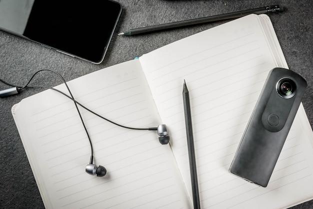 Офис, черный рабочий стол с техникой. , блокнот, панорамные ручки камеры (карандаши), смартфон и наушники на столе.