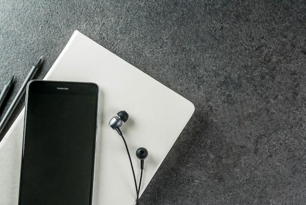 Офис, черный рабочий стол с техникой. , блокнот, ручки (карандаши), смартфон и наушники на столе.