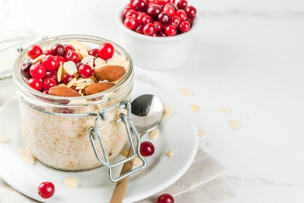 冬の健康的な朝食のレシピ、クリスマスの朝のアイデア。アーモンド、クランベリー、砂糖を一晩オートミール。 。コピースペース