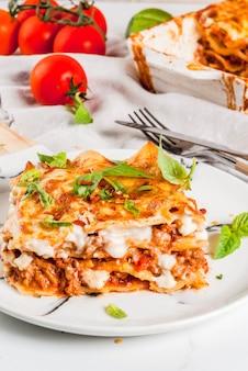 イタリア料理のレシピ。クラシックなラザニアボロネーゼとベシャメルソース、パルメザンチーズ、バジル、トマトを添えたディナー、白い大理石のテーブル、クーピースペース