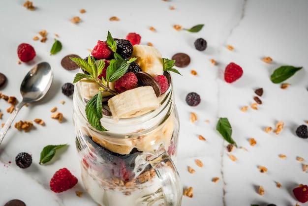 Летний фруктово-ягодный завтрак. здоровый банановый сплит завтрак со сливочным сыром и ягодами