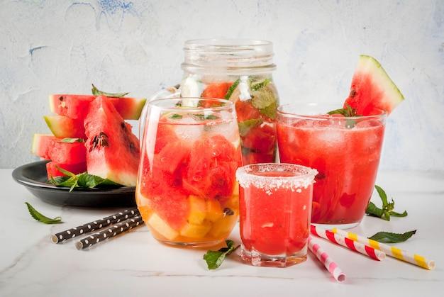 スイカの夏の飲み物とカクテルのセット:サングリア、ジュースクーラーカクテル、注入されたデトックス水、スイカウォッカショット。白い大理石のテーブルの上。コピースペース
