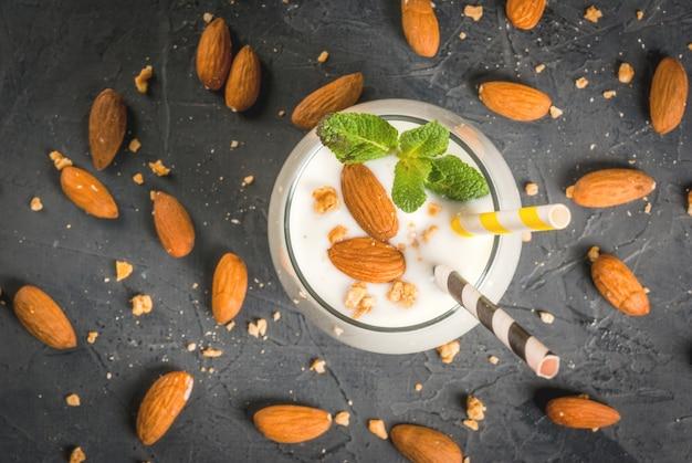 暗いコンクリートのテーブルにミントで飾られたヨーグルト、バナナ、アーモンドナッツから作られた白いスムージー