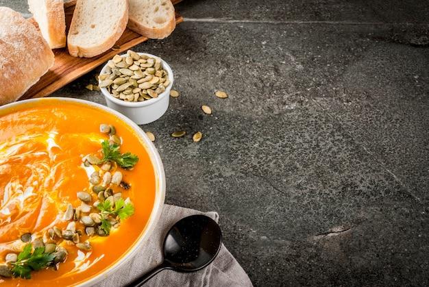 黒い石のテーブルにカボチャの種、クリーム、焼きたてのバゲットとスパイシーなカボチャのスープ