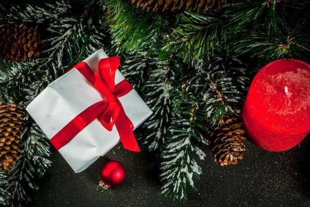 Елочные ветки с эффектом снега с праздничной красной лентой, сосновые шишки, подарочные коробки и свечи, на синем фоне