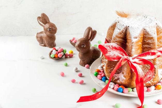 Панеттоне пандоро с праздничной красной ленточкой, пасхальными кроликами и украшениями из сладких конфетных яиц