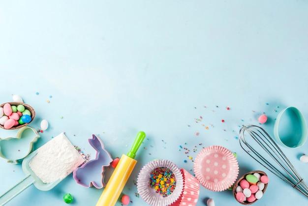 めん棒、ホイップ泡立て器、クッキーカッター、砂糖を振りかける、明るい青の背景に小麦粉