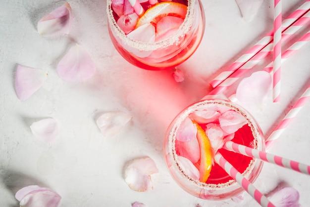 淡いピンクのローズカクテル、ローズワイン、ティーローズの花びら、レモン白い石のコンクリートテーブルの上。