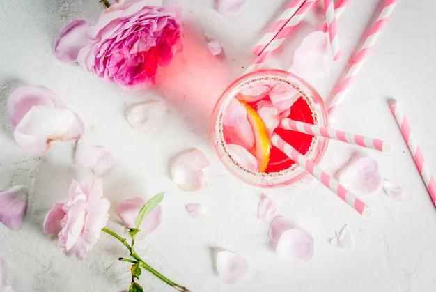 Коктейль светло-розовой розы, с розовым вином, чайными лепестками роз и лимоном. на белом каменном бетонном столе.