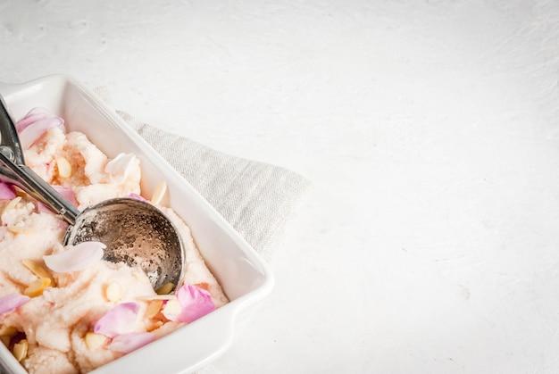 バラの花びらと白いサービングボウルにアーモンドのスライスとアイスクリーム