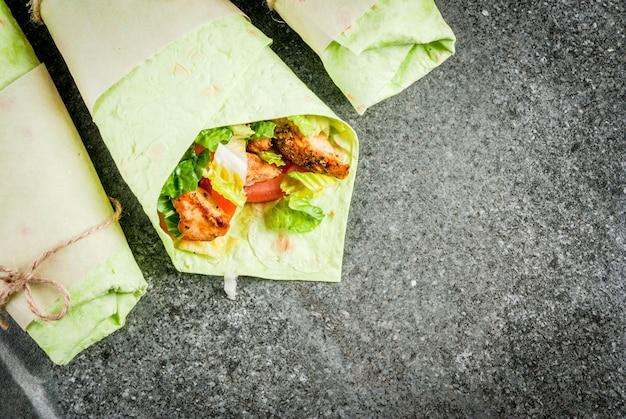 チキン、野菜、ヨーグルトソースが入ったグリーンラヴァッシュトルティーヤのサンドイッチ
