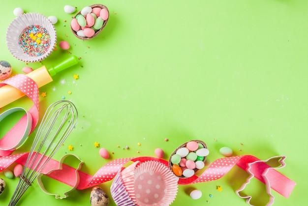 めん棒、泡立て器用の泡立て器、クッキーカッター、砂糖を振りかけると明るい緑の背景に小麦粉