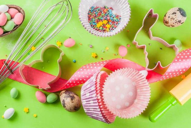 Скалка, венчик для взбивания, печенья, сахарная посыпка и мука на светло-зеленом фоне