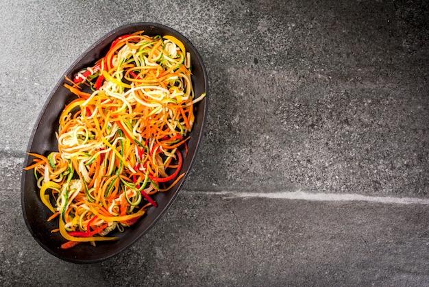 Овощная лапша, макароны из моркови, цуккини и болгарского перца на каменном столе.