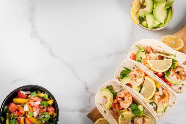 シーフード。メキシコ料理。伝統的な自家製サルササラダ、パセリ、新鮮なレモン、アボカド、エビのグリルポテト付きのトルティーヤタコス。白い大理石の背景に。