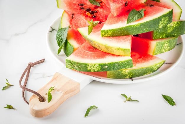 Свежий спелый сочный органический сырой арбуз, нарезанный на кусочки на белой мраморной тарелке