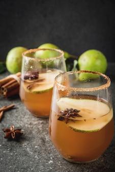 グリューワイン。ナシ、サイダー、チョコレートシロップ、シナモン、アニス、ブラウンシュガーと伝統的な秋のスパイシーなカクテル。黒い石のテーブルの上。