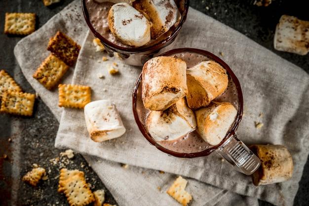 Коктейль из горячего шоколада «у костра» с солеными крекерами и жареным зефиром, в двух кружках, на черном каменном столе,