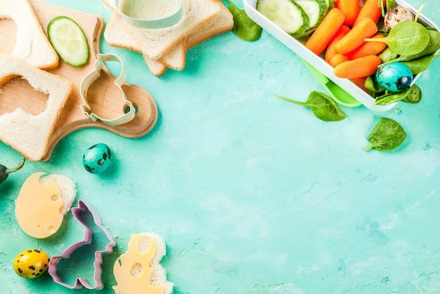 イースターのための創造的な子供の朝食ランチボックス、チーズのサンドイッチ、新鮮な野菜-きゅうり、ニンジン、ほうれん草、カラフルなウズラの卵を調理します。ライトブルーのテーブル、コピースペースのトップビュー