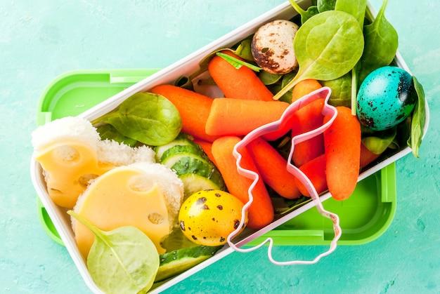 イースターのための創造的な子供の朝食ランチボックス、チーズのサンドイッチ、新鮮な野菜-きゅうり、ニンジン、ほうれん草、カラフルなウズラの卵。ライトブルーのテーブル、コピースペースのトップビュー