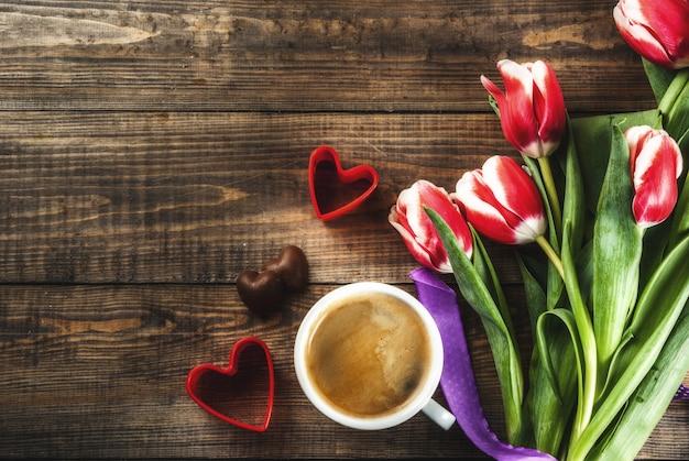 День святого валентина фон для поздравления, открытки. свежие весенние тюльпаны цветы с шоколадными сердечками конфеты и кружка кофе и красные сердечки, на деревянном фоне вид сверху копией пространства
