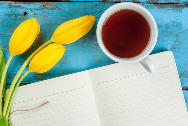 お茶、チューリップ、青いテーブルの上のノート