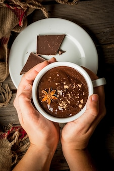 Девушка пьет кружку горячего шоколада, с рождественским подарком на деревенском столе
