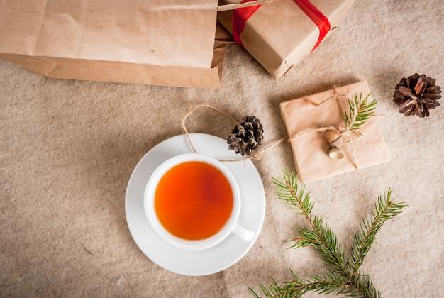ギフト包装と手紙、クリスマスの挨拶のためのカード。手紙、ギフト、クリスマスツリーの枝、松ぼっくりの封筒は、木製のテーブル嘘、香りのよい熱いお茶、トップビュー