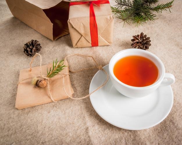 Подарочная упаковка и письма, открытки для рождественских поздравлений. конверты с буквами, подарками, еловыми ветками и сосновыми шишками лежат на деревянном столе, лежат, чашка ароматного горячего чая, вид сверху