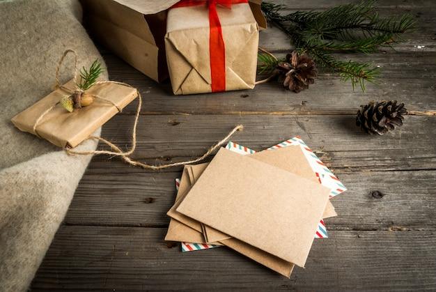 ギフト包装と手紙、クリスマスの挨拶のためのカード。封筒、手紙、ギフト、クリスマスツリーの枝とコーン、上面図、コピースペース