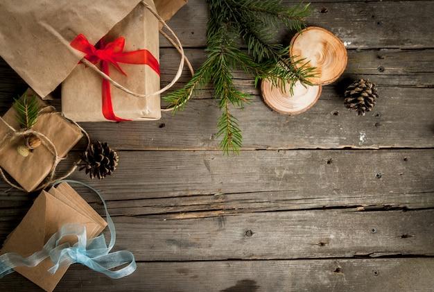 素朴な木製のテーブル、クリスマス、コーン、枝、テーブルのクリスマスの装飾のためのギフトをラッピングします。トップビュー、コピースペース