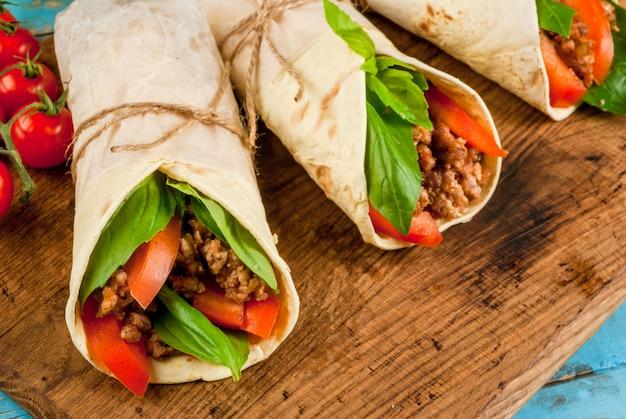 ヘルシーなランチスナック。サンドイッチツイストロールトルティーヤと牛肉と野菜の青い木製の素朴なテーブル、コピースペース、トップビューで木製のまな板