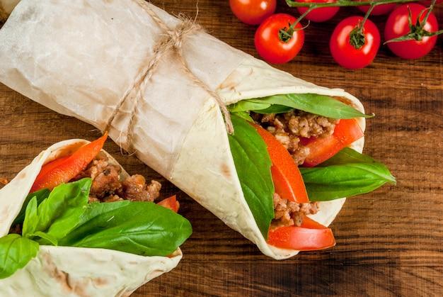 ヘルシーなランチスナック。サンドイッチツイストロールトルティーヤビーフと野菜の青い木製の素朴なテーブル、トップビューで木製のまな板