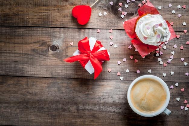 聖バレンタインデー。コーヒー、クリームと砂糖を振りかけたケーキ(ハート)、ギフト、ハートの形の装飾がテーブルにあります。平面図、コピースペース